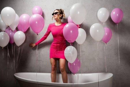 Photo pour Jeune femme en lunettes de soleil et robe debout près des ballons dans le bain - image libre de droit