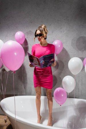 Photo pour Jeune femme dans les lunettes de soleil lecture magazine tandis que debout dans la baignoire près de ballons - image libre de droit