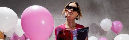 Photo pour Vue à angle bas de la femme élégante dans les lunettes de soleil tenant le magazine près des ballons, bannière - image libre de droit