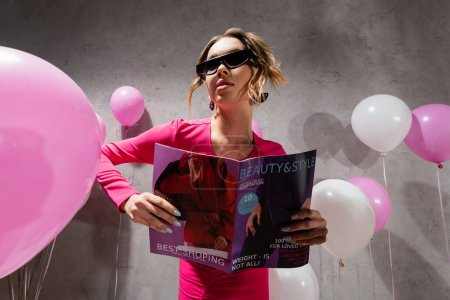 Photo pour Vue à angle bas de la femme élégante tenant magazine de mode près de ballons festifs - image libre de droit