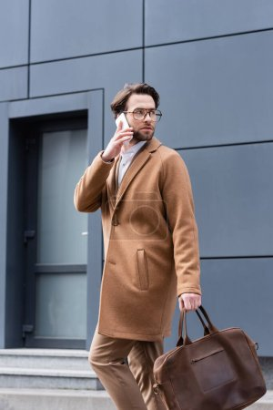 young man in glasses and coat talking on smartphone near building
