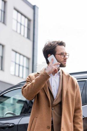 homme d'affaires en lunettes et manteau parlant au téléphone près de la voiture