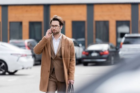 confident man in glasses and beige coat talking on mobile phone in outdoor parking