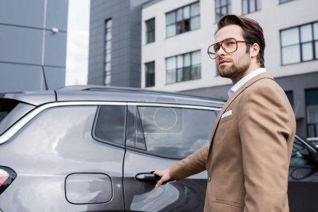 Photo pour Jeune homme d'affaires en costume beige atteignant la porte de la voiture - image libre de droit