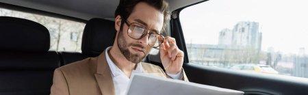 Photo pour Homme confiant réglage des lunettes et la lecture journal d'affaires en voiture, bannière - image libre de droit