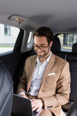 fröhlicher Geschäftsmann mit Brille tippt auf Laptop im Auto