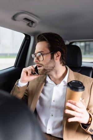 Schockierter Mann in Anzug und Brille hält Pappbecher in der Hand und telefoniert im Auto mit Smartphone