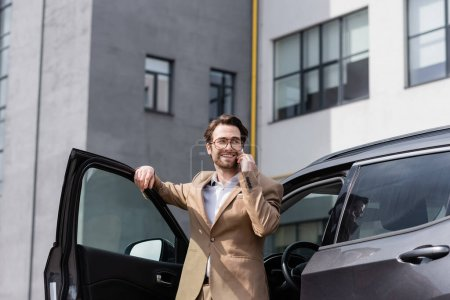 Photo for Cheerful man in suit and glasses talking on smartphone and standing near car with opened door - Royalty Free Image