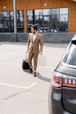 full length of man in suit and glasses walking with suitcase near car on parking