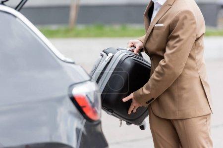 Photo pour Vue recadrée de l'homme en costume mettant valise dans le coffre de la voiture - image libre de droit
