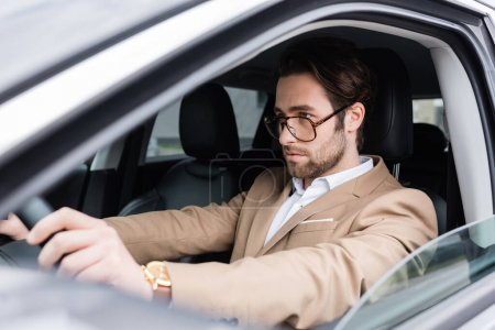 Photo for Bearded man in glasses driving modern car - Royalty Free Image