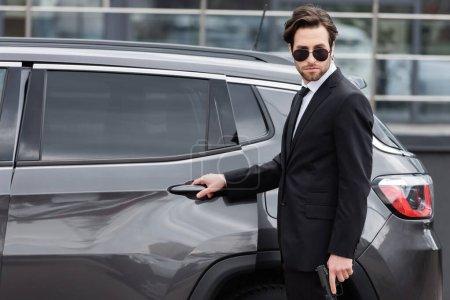 salvaguarda en traje y gafas de sol y traje de arma de mano cerca de auto moderno