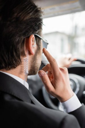 Photo for Back view of bodyguard in sunglasses pointing at security earpiece while driving modern automobile - Royalty Free Image