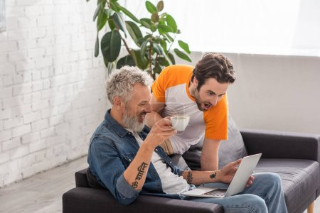 Photo for Excited man with coffee looking at laptop near father on couch - Royalty Free Image