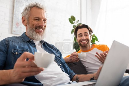 Smiling man holding coffee near son and blurred laptop