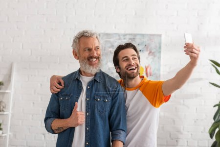 Man showing like gesture while son taking selfie on smartphone