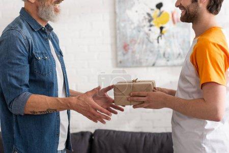 Photo pour Vue recadrée du fils donnant cadeau au père souriant - image libre de droit