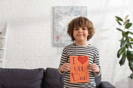 Smiling boy holding gift card with i love you dad lettering