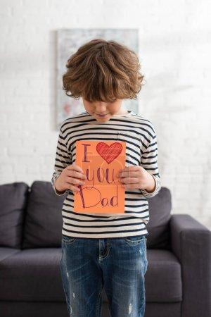 Photo pour Garçon regardant carte-cadeau avec je t'aime papa lettrage à la maison - image libre de droit