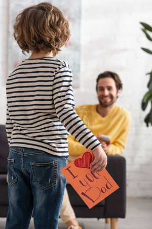 Boy holding gift card with i love you dad lettering near blurred father