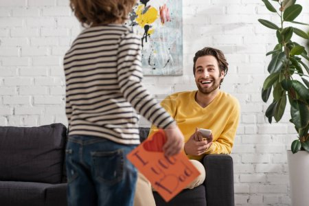 Smiling man with smartphone looking at son with gift card