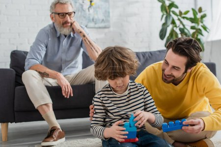 Smiling man holding building block near son and blurred father at home
