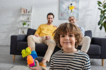 Boy with building blocks looking at camera near parents on blurred background