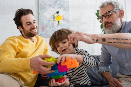 Vater und Großvater spielen mit Kind Bauklötze