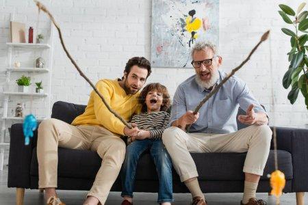 Aufgeregter Junge beim Angeln mit Vater und Großvater zu Hause