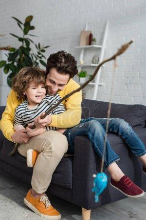 Glücklicher Vater und Kind beim Spielzeugangeln auf der Couch
