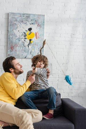 Vater umarmt Kind mit Spielzeug-Angelrute im Wohnzimmer