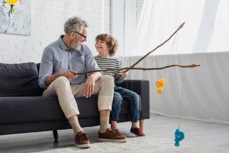 Lächelnder Opa und Junge schauen einander beim Spielzeugfischen an