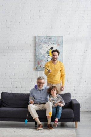 Lächelnde Männer beim Spielzeugangeln mit Kind auf Couch