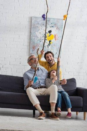 Fröhliche Männer und Jungen mit Spielzeug-Angelruten zu Hause