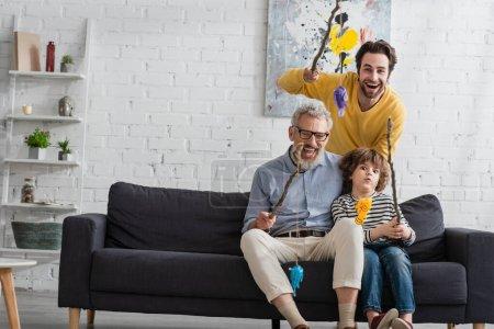 Glückliche Eltern mit Jungen, die Angelruten mit Spielzeugfischen in der Hand halten