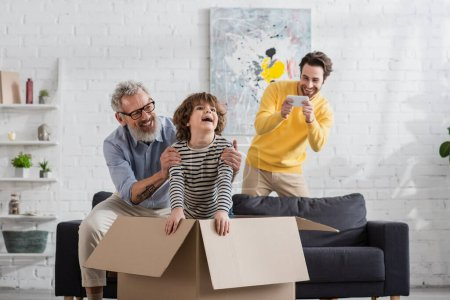 Mature man hugging cheerful grandson in cardboard box near son taking photo at home