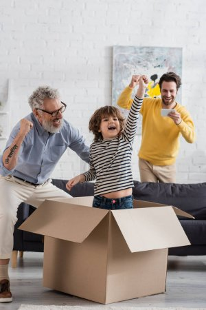 Photo for Excited kid showing yes gesture in carton box near parent with smartphone and grandfather - Royalty Free Image