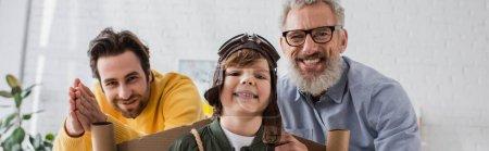 Photo pour Garçon souriant en costume d'aviateur debout près des parents, bannière - image libre de droit