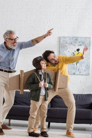 Lächelnder Vater und Großvater zeigen auf Kind im Fliegerkostüm
