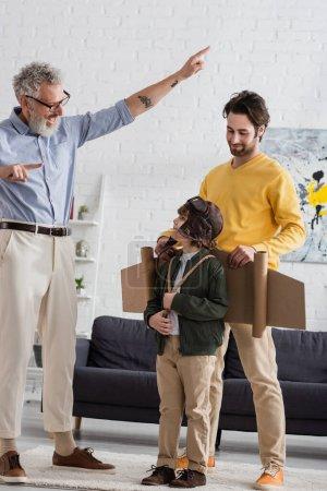 Fröhlicher Opa zeigt mit Fingern auf Jungen im Fliegerkostüm und Sohn