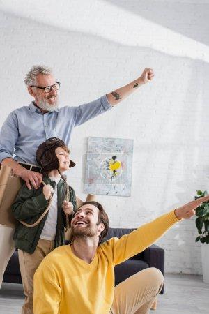 Positive Eltern gestikulieren neben Junge mit Fliegerhelm und Flügeln