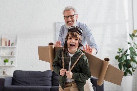 Photo pour Garçon excité en costume d'aviateur jouant près de grand-père flou - image libre de droit