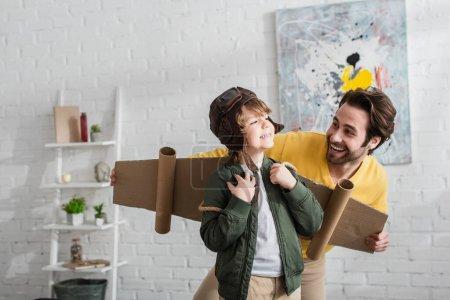 Lächelnder Junge im Fliegerkostüm neben glücklichem Vater
