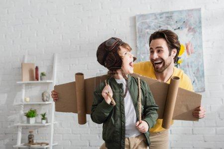 Photo pour Enfant excité dans les ailes de carton et casque d'aviateur debout près de papa à la maison - image libre de droit