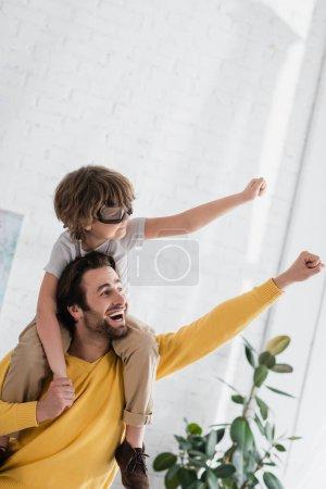 Fröhlicher Mann spielt mit Sohn in Fliegerbrille zu Hause