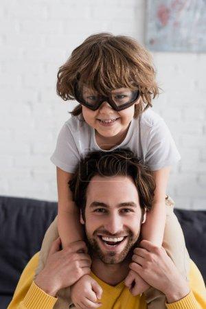 Lächelndes Kind in Fliegerbrille umarmt Vater