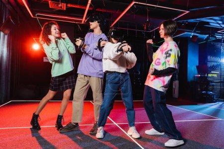 Foto de Adolescentes interracial emocionados mostrando el gesto de ganar cerca de los amigos jugando en auriculares vr - Imagen libre de derechos