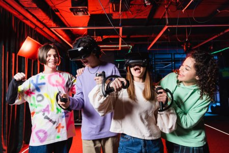 Photo for Happy boy showing win gesture near interracial teenagers in vr game zone - Royalty Free Image
