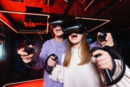 Photo pour Joueurs adolescents excités dans les casques vr s'amuser dans la zone de jeu - image libre de droit