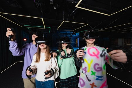 happy and amazed multiethnic friends having fun in vr play room